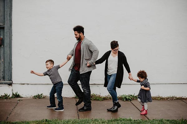 father, mother, daughter and son holding hands and walking on a sidewalk